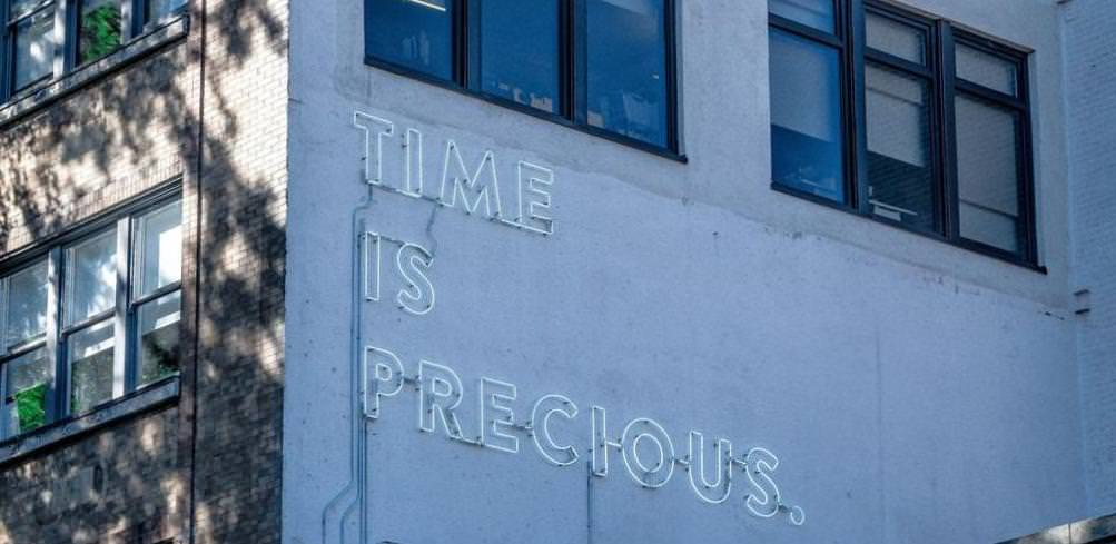 a neon sign saying 'time is precious'