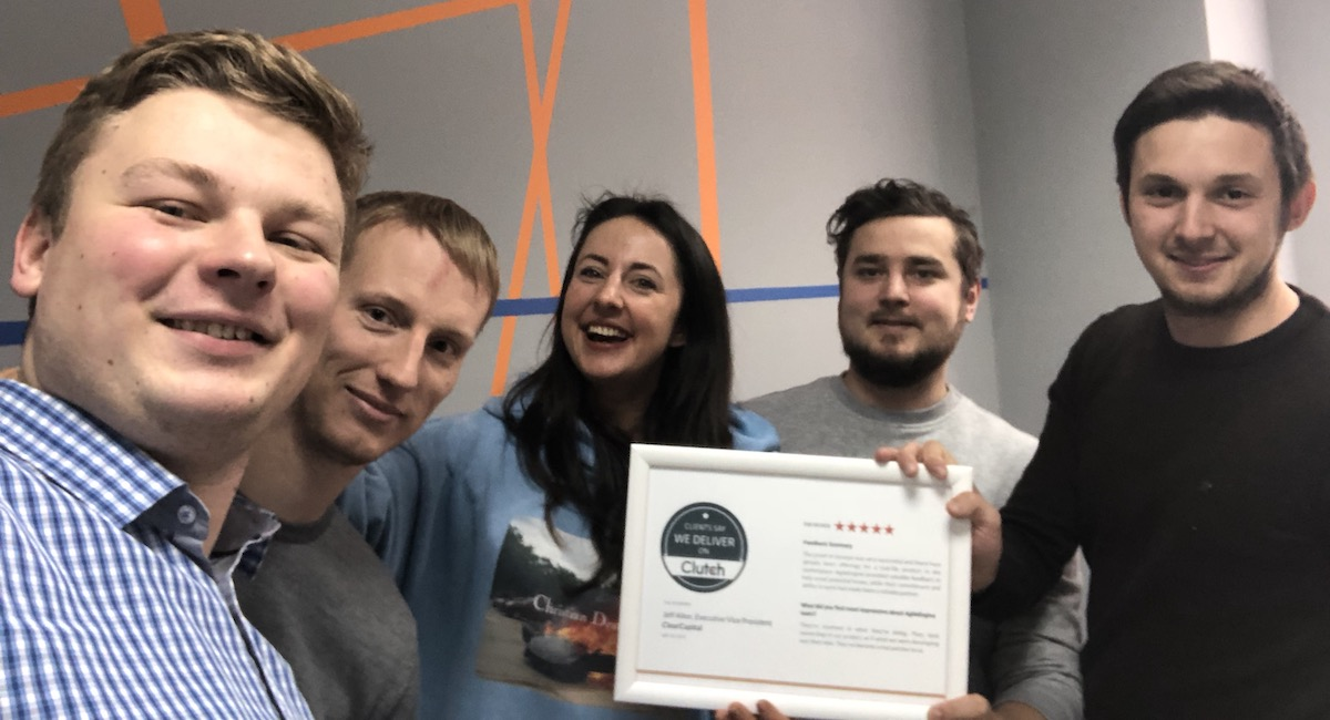 AgileEngine team with a printed client review